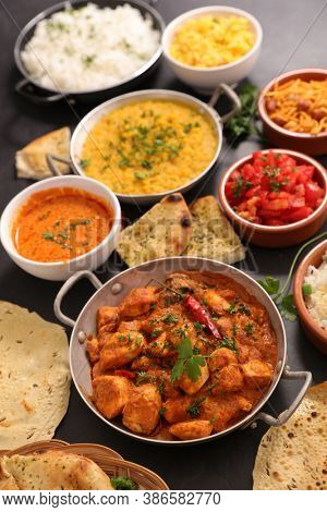 selection of indian dish- naan, curry chicken, curry lentil, tikka masala and rice