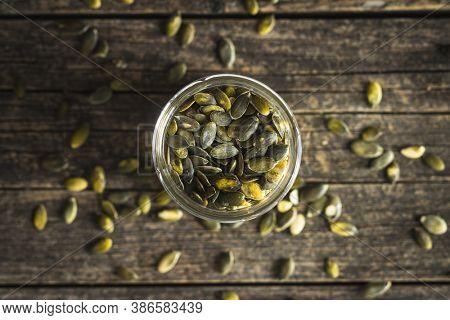 Peeled pumpkin seeds in jar. Top view.