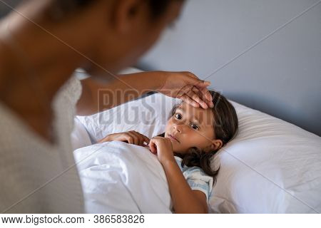 Woman checking temperature with hand of little ill daughter. Mother checking temperature of her sick indian girl. Sick child lying on bed under blanket with woman checking fever on forehead by hand.