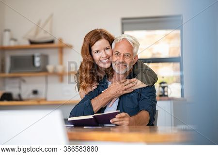 Portrait of happy mature couple at home looking at camera. Romantic wife embracing senior husband from behind while laughing together. Portrait of woman in love hugging  old man in perfect harmony.