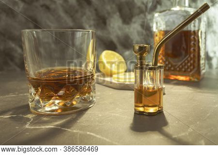 Bong And Whiskey Cognac On The Table. Glass Of Whiskey And Bong With Marijuana