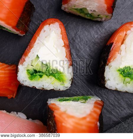 Seafood Delicatessen Salmon Sushi Rolls On Plate. Food Background, Goods Delivery, Japanese Cuisine
