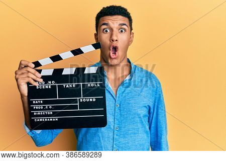 Young arab man holding video film clapboard scared and amazed with open mouth for surprise, disbelief face