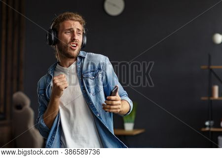 Handsome Long Haired Curly Man With Headphones Listening Music, Singing And Dancing.funny Emotional
