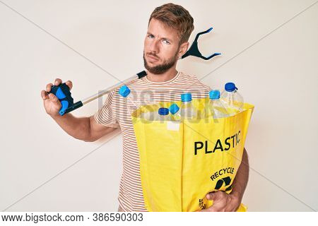Young caucasian man holding recycling bag with plastic bottles and waste picker in shock face, looking skeptical and sarcastic, surprised with open mouth