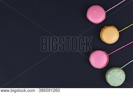 Colorful French Macaron Attached To Strings At Side Of Black Background With Empty Copy Space