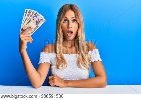 Beautiful blonde young woman holding 5000 japanese yen banknotes scared and amazed with open mouth for surprise, disbelief face