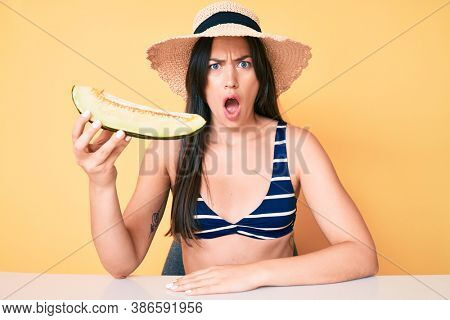 Young beautiful caucasian woman wearing bikini and hat holding slice of melon scared and amazed with open mouth for surprise, disbelief face