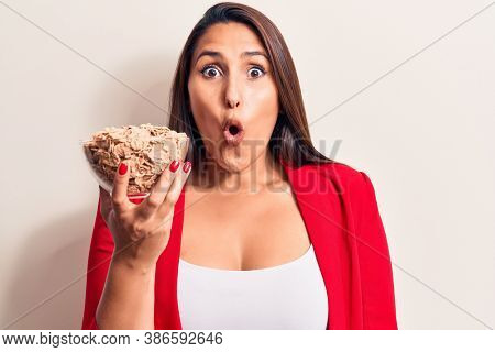 Young beautiful brunette woman holding bowl of cornflakes cereal scared and amazed with open mouth for surprise, disbelief face