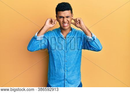 Young arab man wearing casual clothes covering ears with fingers with annoyed expression for the noise of loud music. deaf concept.