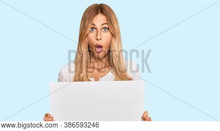 Beautiful blonde young woman holding blank empty banner scared and amazed with open mouth for surprise, disbelief face