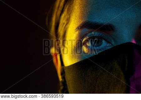 health, safety and pandemic concept - close up of young woman wearing reusable protective mask over black background
