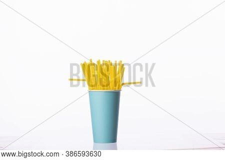 Bunch Of Yellow Plastic Straws In Blue Disposable Biodegradable Paper Cup Copy Space Isolated On Whi