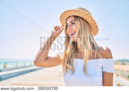 Young blonde tourist girl smiling happy looking to the side walking at the promenade.