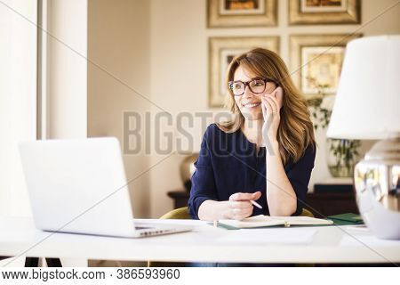 Confident Businesswoman Sitting At Office Desk And Making A Phone Call While Working From Home. Home