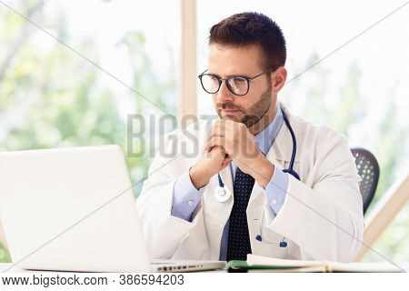 Male Doctor Sitting At Desk And Using Laptop While Working In Doctor's Office