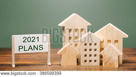 A Poster With The Words Plans 2021 And Wooden Houses. Real Estate Planning And Financing Concept. Ho
