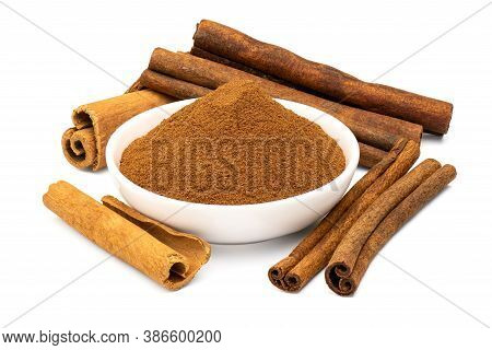 Ground Cinnamon In White Ceramic Bowl And Cinnamon Sticks Isolated On White Background. Close-up And