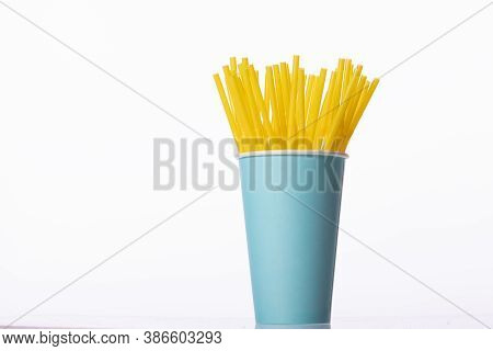 Bunch Of Yellow Plastic Straws In Blue Disposable Biodegradable Paper Cup Isolated On White Backgrou