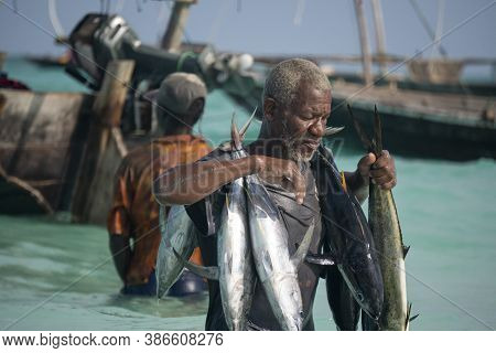 Nungwi, Zanzibar, Tanzania, Africa - January 2020: Black African Man Is Carrying Tuna Fish On The St
