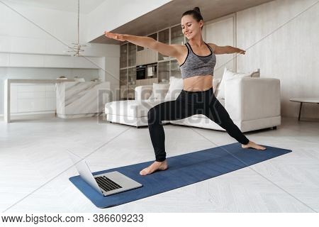 Sporty Woman Practicing Yoga At Home Because Of Social Distancing, Using Laptop For Online Class, St