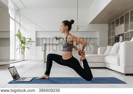 Full Length Shot Of Fit Energetic Young Woman Training At Home Because Of Social Distancing, Practic