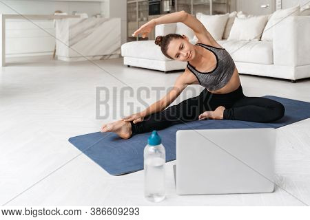 Happy Beautiful Female Enjoy Practicing Yoga At Home, Stretching On Exercise Mat. Coach Showing Exer