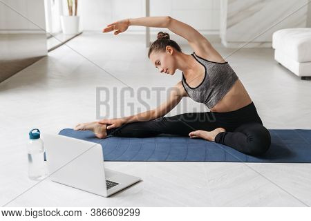 Young Sporty Woman Exercising While Sitting On Yoga Mat In Her Apartment. Active Fit Female Doing St