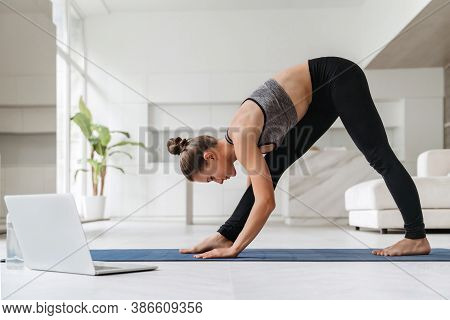 Amazing Young Beautiful Brunette Fitness Woman Doing Stretching Exercises Indoors At Home Near Lapto