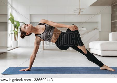 Young Athletic Woman In Sportswear Doing Side Plank Exercise With Twist While Training At Her Room.