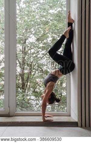 Confident Slim Brunette Woman In Sportswear Doing Handstand Against Wall Near Big Window. Full Lengt