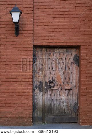 Antique Wooden Door With Metal Hinges On A Red Brick Wall