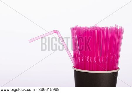 Pink Plastic Straws In Black Disposable Paper Cup Isolated On White Background. One Flexible Straw A