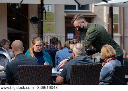 Vilnius, Lithuania - September 20 2020: Waiter With A Mask Serving At The Table At An Outdoor Bar, C