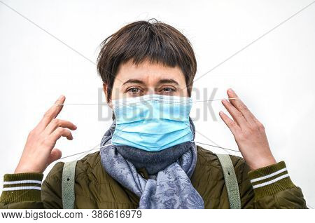 Young Brunette Woman In Outerwear Putting Disposable Blue Medical Mask While Walking. Serious Gaze I