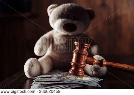 Payments Alimony. Wooden Judge Gavel, Dollar Banknotes And Teddy Bear In A Dark Room. Divorce Concep