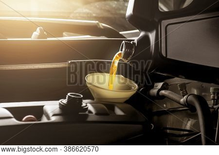 Mechanic Man Pouring Engine Oil To Car Engine