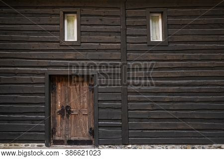 Wall Of Dark Wooden Beams , Small Windows And Vintage Door