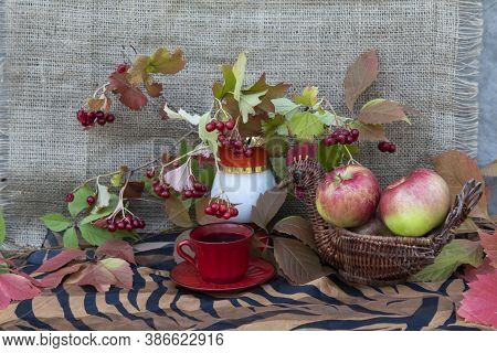 On A Brown Cloth, There Is A Cup Of Coffee, A Bouquet With Viburnum Leaves And Berries. Nearby Are A