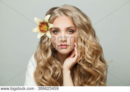 Attractive Young Woman With Long Healthy Curly Hair And Flower On White Background