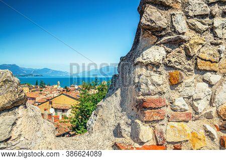 View Of Historical Centre Desenzano Del Garda Old Town, Lake And Mountain Range Through Merlons Of B