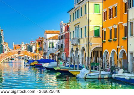 Chioggia Cityscape With Narrow Water Canal Vena With Moored Multicolored Boats Between Old Colorful