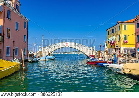 Stone Bridge Ponte Di Vigo Across Vena Water Canal With Colorful Boats And Old Buildings In Historic
