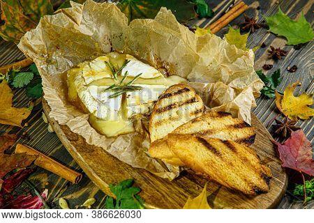 Camembert Baked With Rosemary And Bread Croutons Lies On A Wooden Board