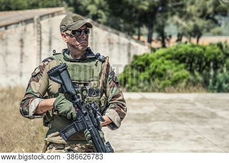 Navy Seals Fighter In Ballistic Goggles, Equipped Military Ammunition And Body Armour, Holding Servi