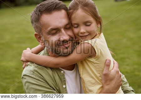 Portrait Of Young Loving Father And His Cute Little Girl Keeping Eyes Closed And Hugging While Spend