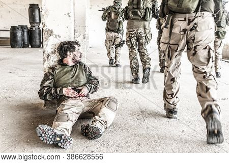 Wounded On Stomach Soldier, Sitting At Floor, Squeezing Bleeding Wound, Hiding Behind Concrete Colum