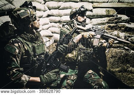 Soldiers Covering From Enemy Fire In Trench. Two Navy Seals Fighters, Infantrymen In Camouflage Unif
