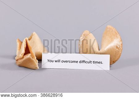 Motivational Text On Paper Saying 'you Will Overcome Difficult Times' Next To Fortune Cookies On Gra