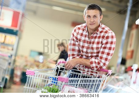 man with shopping cart with food produces in supermarket